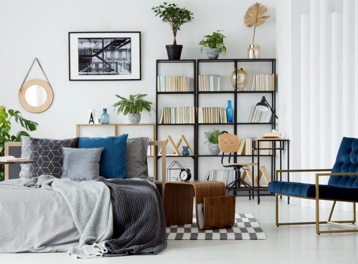 A cozy bed in the middle of a bright modern apartment interior with designer furniture and decor, workspace with bookcase and plants